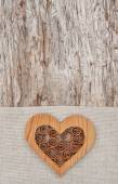 Wooden decorative heart on the linen fabric and old wood — Stock Photo