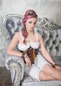 Beautiful steampunk woman on the sofa — Stock Photo