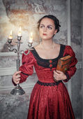 Beautiful woman in medieval dress with candelabrum — Stock Photo
