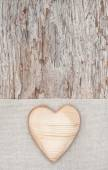 Wooden heart on the linen fabric and old wood — Photo
