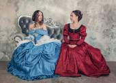 Two beautiful women in medieval dresses on the sofa — Stock Photo