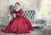 Beautiful woman in red medieval dress on the sofa — Stock Photo