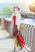 Beautiful girl with shopping bags talking on the mobile phone  — Stok fotoğraf