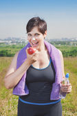 Fitness plus size woman with bottle of water eating apple  — Foto de Stock