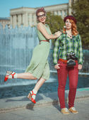 Two beautiful hipster girls with retro camera — Stock Photo