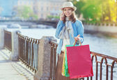 Beautiful girl with shopping bags talking on the mobile  — Stock Photo