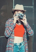 Hipster girl making picture with retro camera, focus on camera — Stock Photo