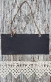 Chalkboard with lacy ribbon on the old wood — Stock Photo