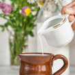 Man hand pouring milk in the mug — Stock Photo #58517057