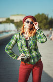 Hipster girl in hat and sunglasses with retro camera — Stock Photo