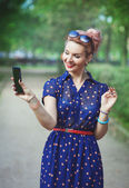 Beautiful woman in fifties style with braces taking picture of h — Stock Photo