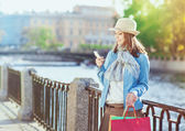 Beautiful girl with shopping bags and mobile phone — Stockfoto