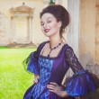Beautiful woman in blue medieval dress winking — Stock Photo #59747369