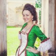 Beautiful woman in green medieval dress winking — Stock Photo #59747389