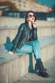 Young fashion beautiful girl in leather jacket and sunglasses — Stock Photo