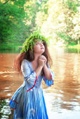 Beautiful woman with long medieval dress praying in the water  — Stock Photo