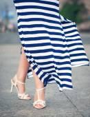 Legs of woman dressed long fluttering striped dress  — Stock Photo
