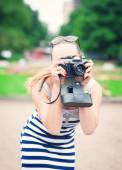 Beautiful young woman in striped dress with old retro camera  — Stock Photo