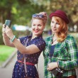Two hipster girls with braces taking pictures of themselves on m — Stock Photo #67328005