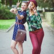 Two hipster girls with braces taking pictures of themselves on m — Stock Photo #67745343