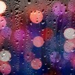Drops of rain on glass with defocused lights. Abstract backgroun — Stock Photo #68185203