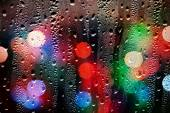 Drops of rain on glass with defocused lights. Abstract backgroun — Stock Photo