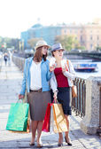 Two beautiful girls with shopping bags and cup of coffee — Foto de Stock