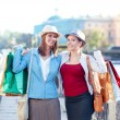 Two happy beautiful girls with shopping bags embrace in the city — Stock Photo #68444609