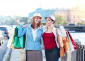 Two happy beautiful girls with shopping bags embrace in the city — Stock Photo