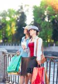 Two beautiful girls with shopping bags and cup of coffee in the  — Foto de Stock