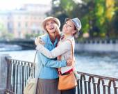 Two beautiful girls laughing and hug in the city — Stock Photo