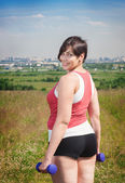 красивый плюс женщина размера, тренирующаяся с гантелями — Стоковое фото