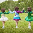 Three girls in irish dance dress and wig posing outdoor — Stock Photo #72811675