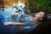 Young beautiful drowned woman lying in the water — Stock Photo