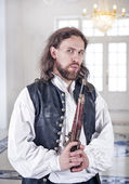 Young handsome man in medieval clothes with pistol — Stock Photo