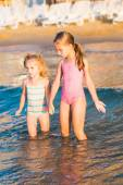 Two adorable kids playing in the sea on a beach — Stock Photo