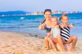 Mother with her daughters at the seashore — Stock Photo