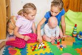 Happy kids playing with little brother — Zdjęcie stockowe