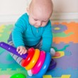 Cute little baby playing with colorful toys — Stock Photo #57383805