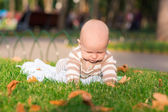 Cute little baby lying in the park — Stockfoto