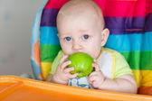 Adorable baby eating apple in high chair — Stock Photo