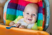 Adorable baby eating in high chair — Stock Photo
