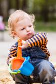 Cute baby boy playing with sand — Stock Photo