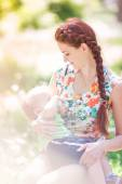 Beautiful happy mother breastfeeding outdoor — Stock Photo