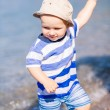 Cute little baby boy exploring the beach — Stock Photo #76288507