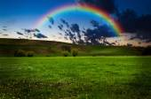 Beautiful field with rainbow at sunset or sunrise — Stock Photo