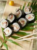 Sushi rolls on wooden plate — Stock Photo