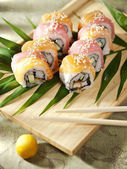 Sushi rolls on a wooden board — Stock Photo