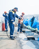 Workers waterproofing of seams on bridge — Stock Photo