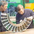 Постер, плакат: Mechanics assembles parts for aviation engine